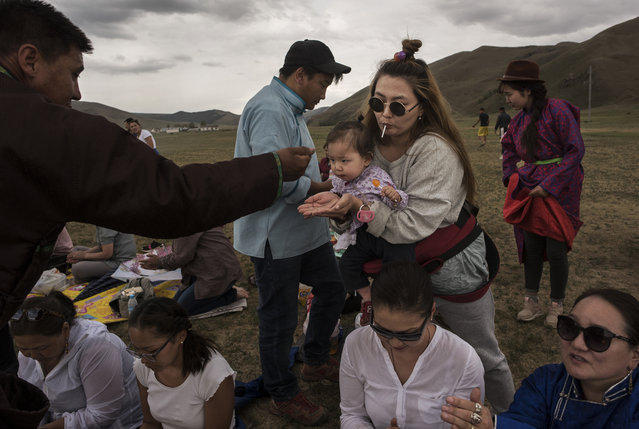 A Mongolian followers of Shamanism or Buu murgul, takes rice as a blessing during a ceremony in the grasslands on June 21, 2018 outside Ulaanbaatar, Mongolia. (Photo by Kevin Frayer/Getty Images)