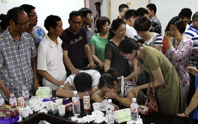 The parents of Wang Linjia, center, are comforted by parents of other students who were on Asiana Airlines Flight 214, at Jiangshan Middle School in Jiangshan city, in eastern China's Zhejiang province. Chinese state media have identified the two people who died in the plane crash at San Francisco International Airport on Saturday as Ye Mengyuan and Wang Linjia, students at the middle school. (Photo by Associated Press)