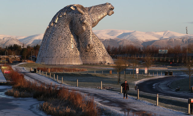 A man walks through the morning frost past the Kelpies in Falkirk, Central Scotland on January 8, 2021. (Photo by Andrew Milligan/PA Images via Getty Images)