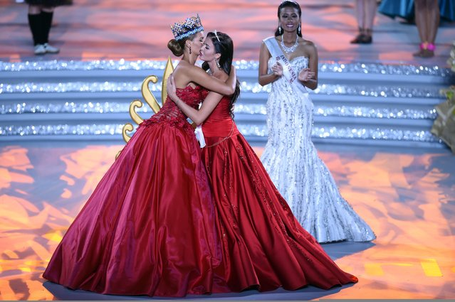 Former Miss World Jolene Strauss (L) and  Miss Russia, Sofia Nikitchuk hug during the Miss World Grand Final in Sanya, in southern China's Hainan province on December 19, 2015. (Photo by Johannes Eisele/AFP Photo)