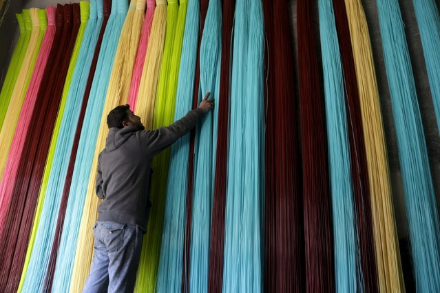 A man adjusts plastic strings, used to produce mats, inside a mat factory in the rebel-controlled area of Maarshureen town in Idlib province, Syria, December 22, 2015. (Photo by Khalil Ashawi/Reuters)