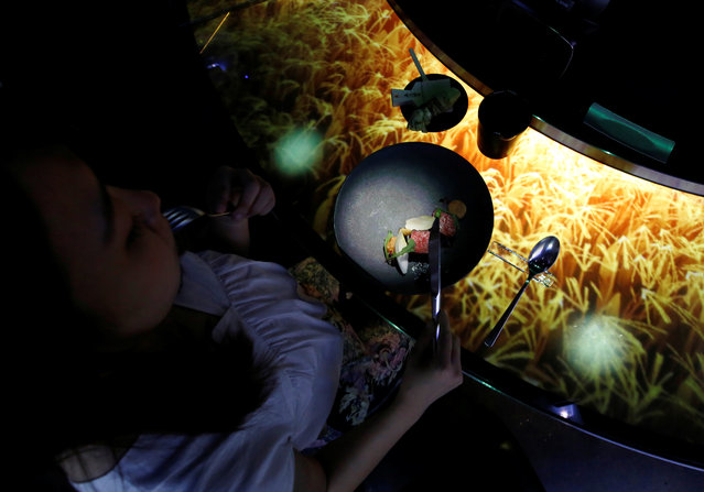 """A woman dines while the projection mapping is cast on a table during its media preview at """"TREE BY NAKED, yoyogi park"""" restaurant in Tokyo, Japan on July 19, 2018. (Photo by Kim Kyung-Hoon/Reuters)"""