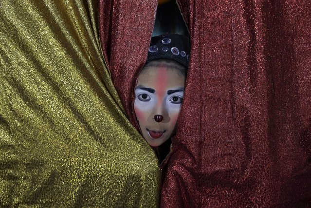 "In this July 20, 2018 photo, Joshep Balta, a clown named ""Cachupito"", peers through the tent curtain to see how many people are waiting for the show, put on by the International Circus, set up in the shanty town of Puente Piedra on the outskirts of Lima, Peru. Balta, a 12-year old clown whose parents work at the circus setting up and breaking down the encampment, was discovered by the circus two years ago when he was performing as a clown at street corners. (Photo by Martin Mejia/AP Photo)"