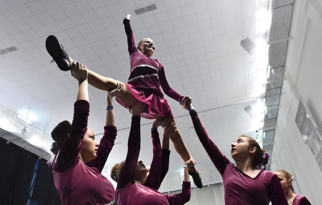 Members of a cheerleading team warm- up during the Russian Cheerleading Championship of students in Moscow on November 20, 2016. (Photo by Natalia Kolesnikova/AFP Photo)