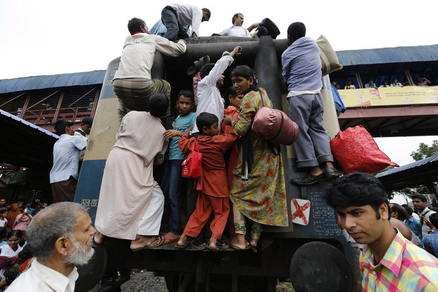 Passengers climb on board an overcrowded train at a railway station in Dhaka August 8, 2013. Millions of residents in Dhaka are travelling home from the capital city to celebrate the Muslim Eid al-Fitr holiday, which marks the end of the holy fasting month of Ramadan. (Photo by Andrew Biraj/Reuters)