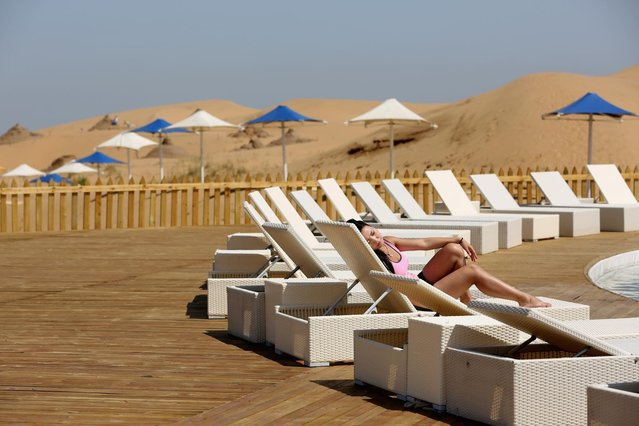 A woman rest beside a swimming pool in Xiangshawan Desert, also called Sounding Sand Desert on July 20, 2013 in Ordos of Inner Mongolia Autonomous Region, China. Xiangshawan is China's famous tourist resort in the desert. It is located along the middle section of Kubuqi Desert on the south tip of Dalate League under Ordos City. Sliding down from the 110-metre-high, 45-degree sand hill, running a course of 200 metres, the sands produce the sound of automobile engines, a natural phenomenon that nobody can explain. (Photo by Feng Li/Getty Images)
