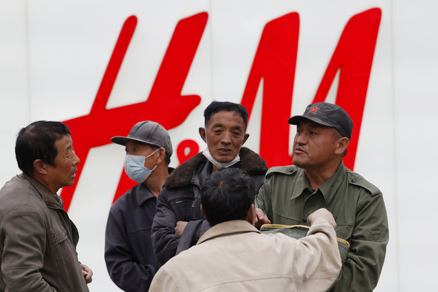 Migrant workers gather near an H&M store in Beijing on Monday, March 29, 2021. China stepped up pressure Monday on foreign shoe and clothing brands to reject reports of abuses in Xinjiang, telling companies that are targeted by Beijing for boycotts to look more closely and pointing to a statement by one that it found no forced labor. (Photo by Ng Han Guan/AP Photo)