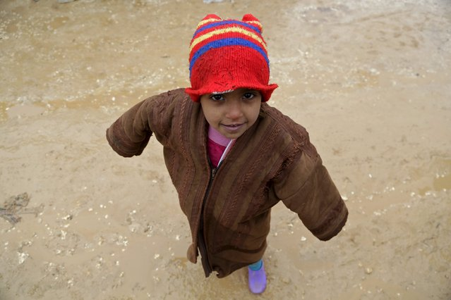 Six-year-old Abeer stands outside tents housing internally displaced people, during the cold weather in Jerjnaz camp, in Idlib province, Syria, January 5, 2016. (Photo by Khalil Ashawi/Reuters)
