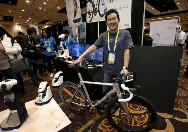 """Satoshi Yanagisawa of Japan displays the Orbitrec, a connected 3D printed bicycle by Cerevo, during """"CES Unveiled,"""" a preview event of the 2016 International CES trade show, in Las Vegas, Nevada January 4, 2016. The bicycle features 3D printed titanium joints, carbon fiber tubes and a built in sensor module that sends a variety of information to a smartphone. (Photo by Steve Marcus/Reuters)"""