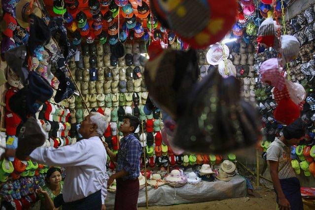 A man buys a cap at a shop at the Kyaik-Khauk pagoda festival in Tanlyin township, outside Yangon, February 2, 2015. (Photo by Soe Zeya Tun/Reuters)