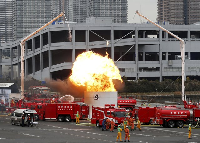A firefighter and rescues perform drills during a New Year demonstration by the fire brigade in Tokyo, Japan, January 6, 2016. (Photo by Yuya Shino/Reuters)