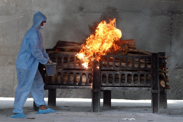 A frontline worker in personal protective equipment (PPE) sprays a flammable liquid on a burning funeral pyre of a man who died from the coronavirus disease (COVID-19), at a crematorium on the outskirts of Mumbai India, April 15, 2021. (Photo by Francis Mascarenhas/Reuters)