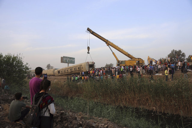 A crane is used to lift a part of a passenger train that derailed injuring some 100 people, near Banha, Qalyubia province, Egypt, Sunday, April 18, 2021. (Photo by Fadel Dawood/AP Photo)