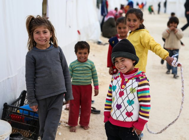 Syrian refugee children who fled violence in Syrian city of Ayn al-Arab or Kobani seen outside their tent in Turkey's newly set-up camp in the border town of Suruc, Turkey, Friday, January 30, 2015. The 35,000 people capacity camp is the biggest refugee camp in Turkey. (Photo by Emrah Gurel/AP Photo)