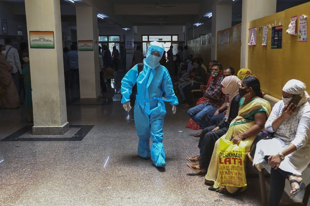 An Indian woman in personal protective suit walks towards a COVID-19 ward of a hospital as others waits for their test results in Hyderabad, India, Thursday, April 29, 2021. (Photo by Mahesh Kumar A./AP Photo)