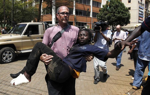 A journalist rescues a woman who was injured in a shootout between armed men and the police. (Photo by Thomas Mukoya/Reuters)