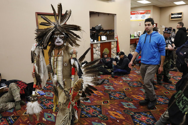 A Native American dancer walks past activists and veterans who are sheltering at the Prairie Knights Casino because of a blizzard hitting the Standing Rock Indian Reservation, near Fort Yates, North Dakota, U.S., December 6, 2016. (Photo by Lucas Jackson/Reuters)