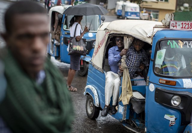 """Passengers look out from an auto-rickshaw, known locally as a """"bajaj"""", in Gondar, in the Amhara region of Ethiopia Sunday, May 2, 2021. (Photo by Ben Curtis/AP Photo)"""