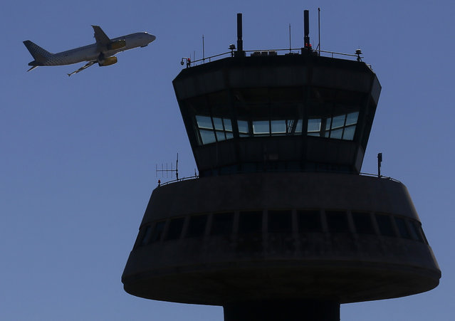 A plane takes off near a control tower at Barcelona's airport February 10, 2015. Shares in Spanish airports operator Aena were priced at the top end of expectations on Tuesday, propelled by strong demand from investors betting on the country's economic recovery. (Photo by Albert Gea/Reuters)