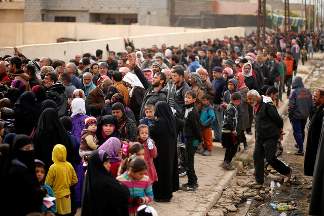 Iraqis wait outside a distribution point run by United Nations agencies at Zahra district, east of Mosul, Iraq December 8, 2016. (Photo by Ahmed Jadallah/Reuters)