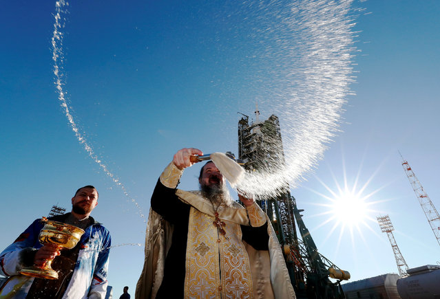 An Orthodox priest conducts a blessing in front of the Soyuz MS-10 spacecraft set on the launchpad ahead of its upcoming launch, at the Baikonur Cosmodrome inKazakhstan, October 10, 2018. (Photo by Shamil Zhumatov/Reuters)