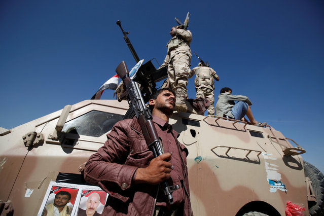 A pro-Houthi soldier tribesman poses for a photo next to a military armoured personnel during a gathering held to mobilize fighters for battles against government forces, in Sanaa, Yemen November 24, 2016. (Photo by Khaled Abdullah/Reuters)