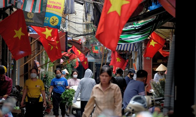 People wearing face masks walk in an alley in Hanoi, Vietnam, 25 May 2021. Hanoi shut down restaurants, hair salons and barbershops on 25 May in oder to prevent the spread of COVID-19 pandemic. (Photo by Luong Thai Linh/EPA/EFE)