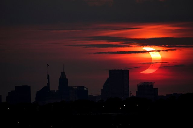 A partial solar eclipse rises over the Baltimore skyline, Thursday, June 10, 2021, seen from Arbutus, Md. (Photo by Julio Cortez/AP Photo)