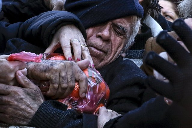 A man grasps a bag of tangerines as people receive free produce, handed out by farmers, during a protest over the government's proposal to overhaul the country's ailing pension system in Athens, Greece, January 27, 2016. (Photo by Alkis Konstantinidis/Reuters)