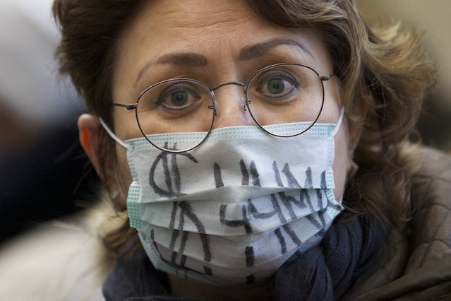 A hard-currency mortgage holder wears a face mask showing a dollar sign and reading Plague during a protest at a bank in Moscow, Russia, Thursday, January 28, 2016. Russians who took out mortgages denominated in a foreign currency are protesting at their banks to demand that the loans be restructured.  They chose foreign currency mortgages years ago to take advantage of lower interest rates abroad, but when Russia's currency collapsed, the cost of repaying those mortgages skyrocketed. (Photo by Ivan Sekretarev/AP Photo)