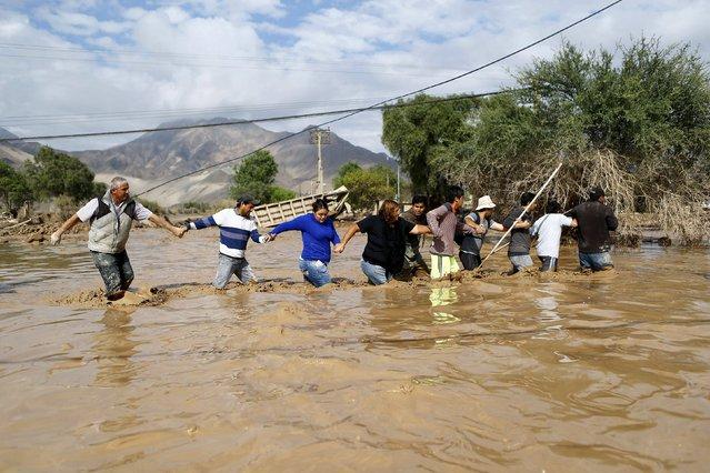 Locals cross a floodeded river at Copiapo city, March 26, 2015. (Photo by Ivan Alvarado/Reuters)