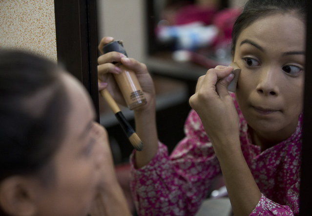 In this June 20, 2018 photo, Johandrys Colls practices makeup during a class at the Belankazar Modeling Academy in Caracas, Venezuela. In Venezuela, competing comes at a high price: elaborate sequined gowns and pricey cosmetic surgeries are out of reach for most in a country where inflation is running in the five digits and state workers earn about $3 a month. (Photo by Fernando Llano/AP Photo)