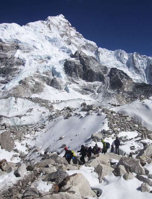 In this  Saturday, March 21, 2015 photo, trekkers walk towards Everest Base camp, Nepal. (Photo by Tashi Sherpa/AP Photo)