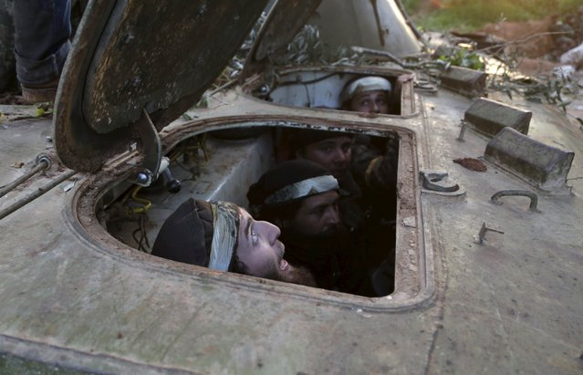 Rebel fighters from the Ahrar al-Sham Islamic Movement sit inside a BMP armoured vehicle during what they said was an offensive to take the northwestern city of Idlib March 24, 2015. (Photo by Khalil Ashawi/Reuters)