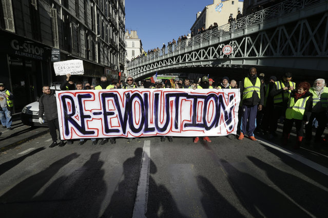 Demonstrators wearing yellow vests hold a banner during a march Saturday, December 8, 2018 in Marseille, southern France. (Photo by Claude Paris/AP Photo)