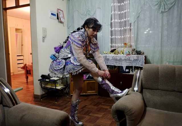 Alicia Vargas, 23, a performer from the Urus Diablada group, tied the laces of her boots before a practice ahead of Carnival in Oruro, Bolivia February 5, 2016. (Photo by David Mercado/Reuters)