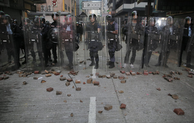 Riot police stand guard as rioters set fires and throw bricks in Mong Kok district of Hong Kong, Tuesday, February 9, 2016. Hong Kong's Lunar New Year celebration descended into chaotic scenes as protesters and police clashed over a street market selling fish balls and other local holiday delicacies. (Photo by Vincent Yu/AP Photo)