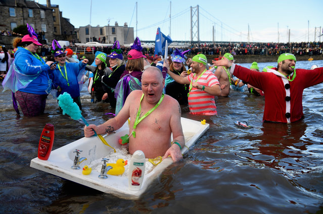 Members of the public wearing fancy dress in the water as they join around 1,000 New Year swimmers, many in costume, in front of the Forth Rail Bridge during the annual Loony Dook Swim in the River Forth on January 1, 2017 in South Queensferry, Scotland. Tens of thousands of people gathered last night in Edinburgh and other events across Scotland to see in the New Year at Hogmanay celebrations. (Photo by Jeff J. Mitchell/Getty Images)