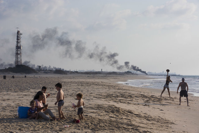 Israelis enjoy the day in Zikim beach, near kibbutz Zikim, on the Israel and Gaza border, as in the background black smoke rises from the tires set on fire by Palestinian protesters near Beit Lahiya, northern Gaza Strip, Monday, October 8, 2018. (Photo by Oded Balilty/AP Photo)