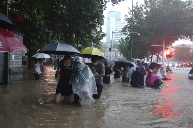 People move through flood water after a heavy downpour in Zhengzhou city, central China's Henan province on Tuesday, July 20, 2021. Heavy flooding has hit central China following unusually heavy rains, with the subway system in the city of Zhengzhou inundated with rushing water and thousands of residents having to be relocated. (Photo by Chinatopix via AP Photo)