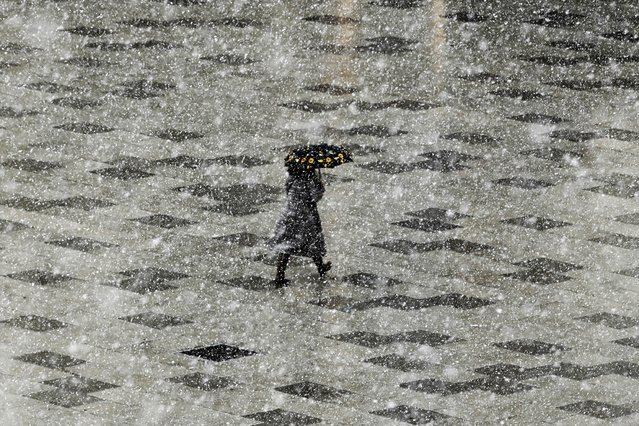 A pedestrian walks with an umbrella through the Mother Teresa square during an unexpected heavy snow fall in the town of Pristina on March 21, 2021. (Photo by Armend Nimani/AFP Photo)