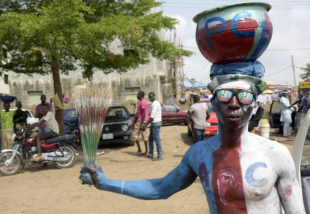A man wears glasses and body paint adorned with the logo of Nigeria's main opposition All Progressives Congress (APC) as residents await results of the presidential election in Abuja, on March 30, 2015.  Nigerians awaited the first results of a closely fought general election, despite protests over the conduct of the vote and calls for calm given fears of a repeat of post-poll violence. (Photo by Pius Utomi Ekpei/AFP Photo)