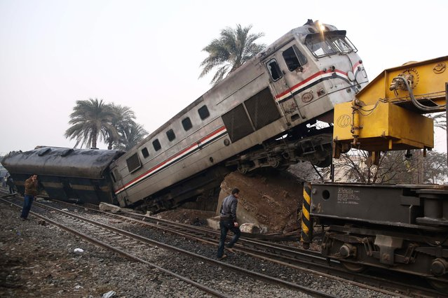 People gather at the site of a train derailment near Beni Suef, Egypt, Thursday, February 11, 2016 that  injured dozens of people were injured as it was traveling north toward Cairo. Railroad accidents due to negligence are common in Egypt. Egyptians have long complained that the government has failed to deal with the country's chronic transport problems. (Photo by Samer Abdallah/AP Photo)
