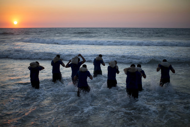 In this Thursday, March 5, 2015 photo, Israeli high-school seniors preparing to join the Israeli military later this year walk into the sea carrying weighted bags during privately run military combat fitness training in Shefayim, central Israel. (Photo by Oded Balilty/AP Photo)