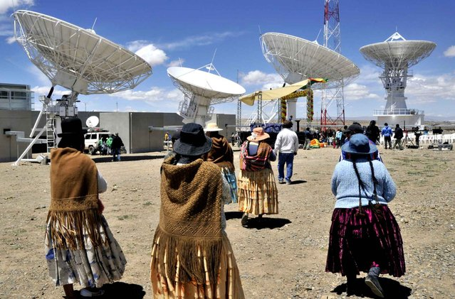 Bolivian Aymara natives attend the inauguration of the first Bolivian communication satellite ground control, in Amachuma, 25 km southeast from La Paz, and at 4,000 m above sea level, on December 2, 2013. The satellite will be launched from China next December 20. (Photo by Aizar Raldes/AFP Photo)