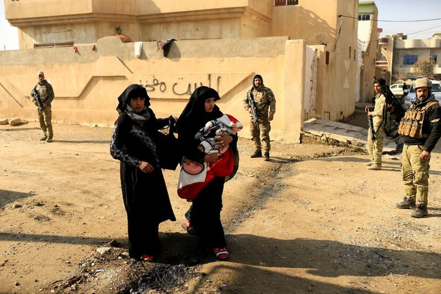 A displaced Iraqi woman, who fled the Islamic State stronghold of Mosul, carries her baby in the Mithaq district of eastern Mosul, Iraq, January 3, 2017. (Photo by Thaier Al-Sudani/Reuters)