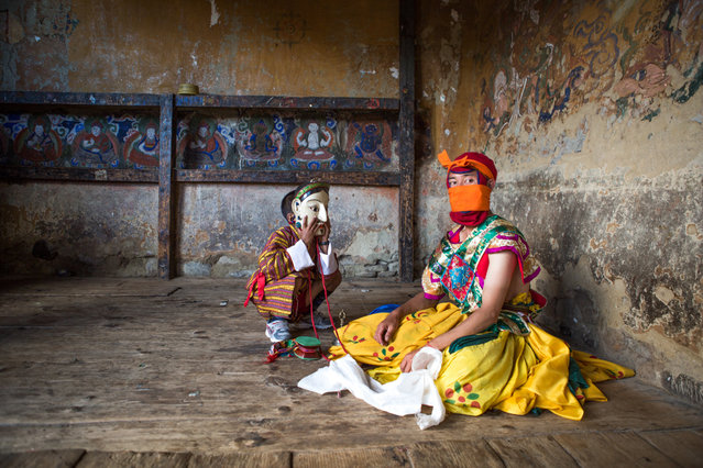 """""""Bhutanese masked dancer and boy"""". A young Bhutanese boy tries on the mask of the dancer seated next to him; the dancer is having a short break after a physically gruelling masked dance at the colourful festival held at the Tamshing Lhakhang (Monastery) in Bumthang, Bhutan. (Photo and caption by Joyce Le Mesurier (Singapore)/2014 Sony World Photography Awards)"""