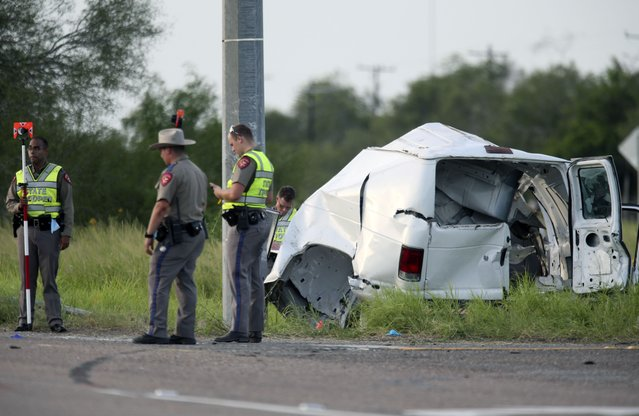 Texas Department of Public Safety officers stand near a vehicle where multiple people died after the van carrying migrants tipped over just south of the Brooks County community of Encino on Wednesday, August 4, 2021, in Encino, Texas. The van crashed against a utility pole after it attempted to turn off of Highway 281 onto Business 281. Encino is about 2 miles (3.22 kilometers) south of the Falfurrias Border Patrol checkpoint. (Photo by Delcia Lopez/The Monitor via AP Photo)