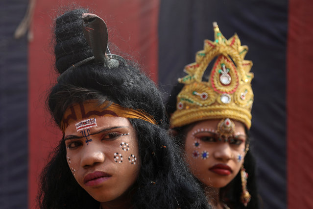 """Children, dressed up as a Hindu God and Goddess, look on as they beg for alms during """"Kumbh Mela"""", or the Pitcher Festival, in Prayagraj, previously known as Allahabad, India, January 14, 2019. (Photo by Anushree Fadnavis/Reuters)"""