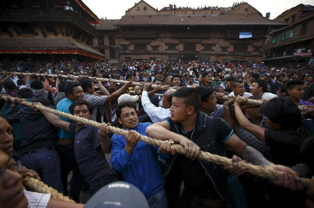 Devotees hold on to the ropes tied to the chariot of God Bhairab as they pull it through the city centre of Bhaktapur near Kathmandu during the Bisket festival April 10, 2015. (Photo by Navesh Chitrakar/Reuters)
